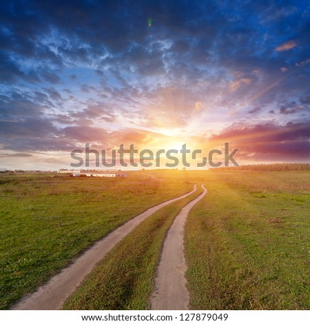 rut road in steppe on sunset background