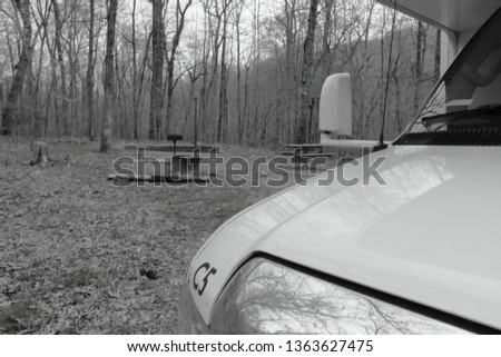RV at campsite in woods. Fits themes for nature, escape, recreational vehicle, camping. #1363627475