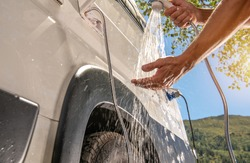 RV Camper Van Outdoor Shower Taking. Caucasian Men Preparing For Shower While on Wilderness Boondocking Camping. Recreational Vehicle Motorhome Outside Water Outlet.