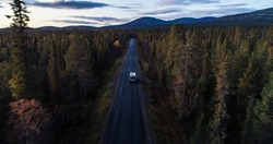 RV in autumn color forest, Aerial drone shot of a Camper van in foliage woods, moving towards Ounastunturit fells, sunny, autumn evening, in Lapland