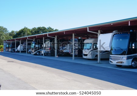 RV recreational vehicle storage parking covered garage filled with many new looking RVs and trailers.