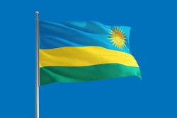 Rwanda national flag waving in the wind on a deep blue sky. High quality fabric. International relations concept.