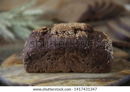 rye bread and ears of rye in soft blur background on wooden rustic background. Close-up. #1417431347