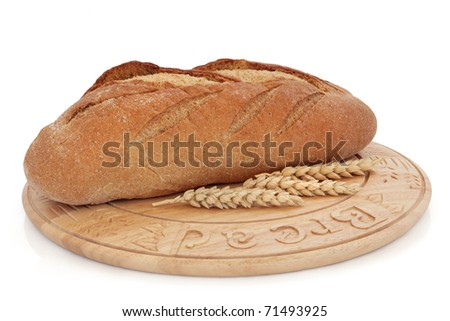 Rye bread loaf on a wooden board with wheat sprigs, over white background. Mass produced bread board.
