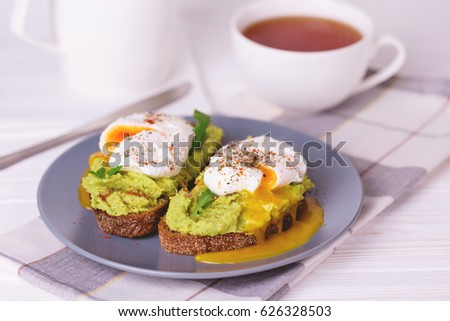 Rye bread toast with poached egg, puree avocado, spices and arugula and cup of tea. Continental breakfast. Healthy food concept. Selective focus