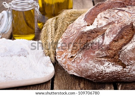 rye bread  with ears of wheat, glass oil and board with flour on old wooden table