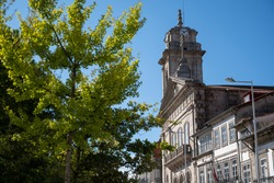 São Pedro Basilica. Old church made of rock. Tree in the foreground and blue sky. Guimarães, Portugal.