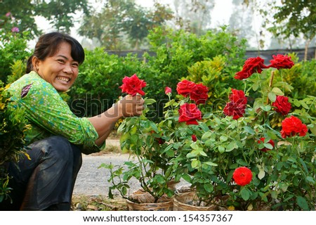SA DEC, VIET NAM, ASIA  - JANUARY 26. Happiness of asia Farmer in springtime, success harvest with beautiful flowerpot for Vietnam Tet ( lunar New Year) in Sadec, Vietnam, Asia. January 26, 2013 #154357367