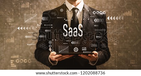 SaaS with businessman holding a tablet computer on a dark vintage background