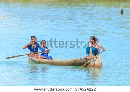 Sabah, Malaysia - November 23, 2014: Unidentified Borneo Sea Gypsy kids on a canoe in Mabul Bodgaya Island, Sabah Borneo, Malaysia. #594524222