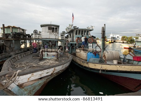 SABAH, MALAYSIA - SEPT 10: Fishing boats and trawlers come to port in the morning to deliver fresh fish and other catches to the fish market in Semporna town on September 10, 2011 in Sabah, Malaysia.