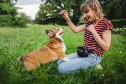 Sable welsh corgi pembroke and his owner, happy and relaxed during a walk in a park, playing and training