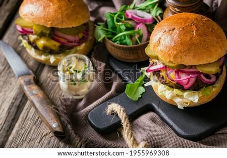 Saborosos hambúrgueres caseiros grelhados com carne, tomate, queijo, bacon e alface em fundo de madeira rústico. conceito de fast food e junk food. Foto stock ©
