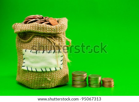 Sack and row of coins over green background - stock photo