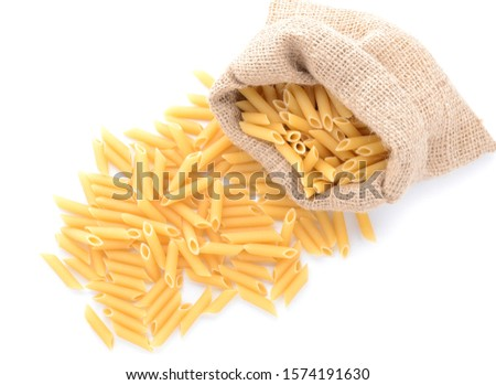 Sack with uncooked pasta on white background