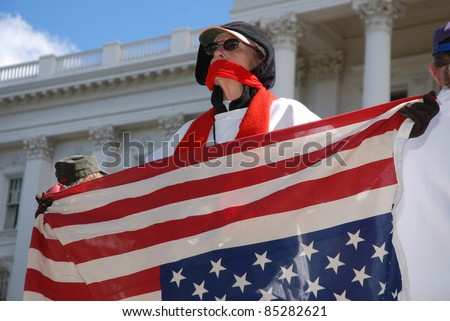 SACRAMENTO, CALIFORNIA - FEBRUARY 26: An unidentified protester with mouth covered holds upsdie-down flag at the California State Capitol during rally in Sacramento, California, on February 26, 2011