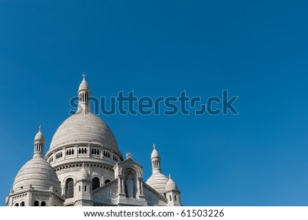 Sacre Coeur and its white domes and spires gleaming white on a clear, blue sky in Paris, France.