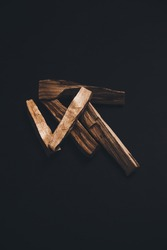 sacred incense of Palo Santo, a composition of sticks and wooden bars of the sacred Palo Santo tree. religious paraphernalia on a black background