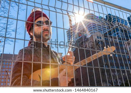 Sacred man with guitar in city sun. A closeup view of a handsome young spiritual guy, standing behind a chain-link fence near modern skyscrapers, holding a small guitar and symbolic eagle feather #1464840167
