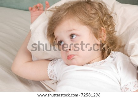 Sad adorable little girl in the bed closeup