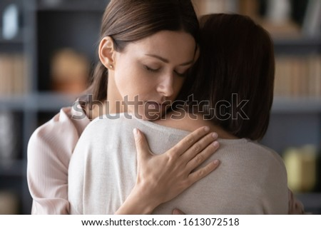 Sad adult daughter hug comfort middle-aged mother make peace reconcile after fight, upset distressed grown-up female embrace caress senior mom show love and care at home, parenting concept