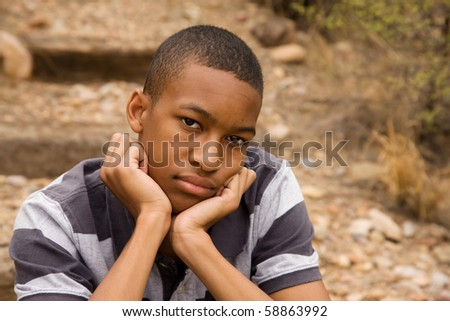 Sad African-American Male sitting in outdoor setting