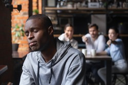 Sad african American millennial guy outcast sit alone suffering from bullying from other people in coffeehouse, depressed black man loner isolated from friends having personal psychological problems