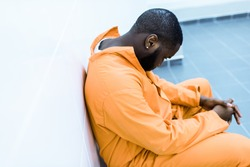 sad african american prisoner sitting on bench in prison cell