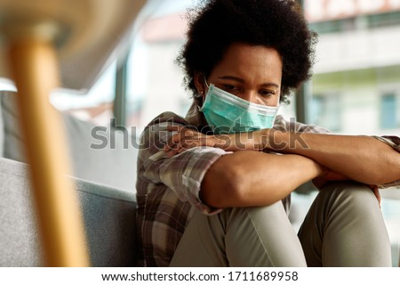 Sad African American woman wearing face mask while sitting at home and thinking of something.