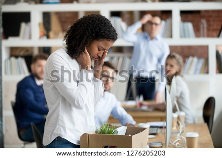 Sad african female young employee packing belongings in box at workplace got fired from job, stressed upset black worker intern leaving office on last day at work crying after unfair dismissal