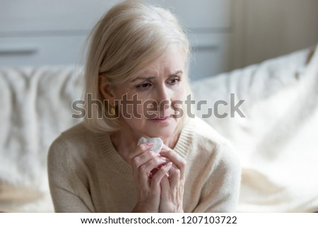 Sad aged lady crying sitting on couch lost in thoughts and memories of past god life, sorrowful senior woman grieve for passed away husband missing him, upset elderly female feel lonely and abandoned