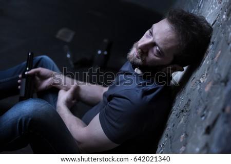 Sad alcoholic expressing desperation indoors