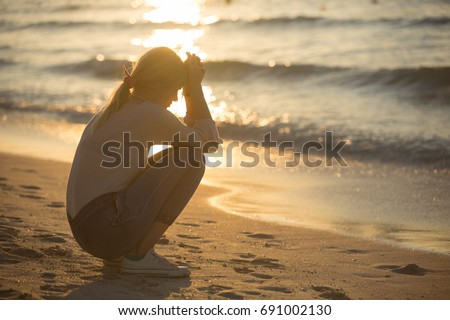 Sad and alone young woman sitting on the beach at sunset.