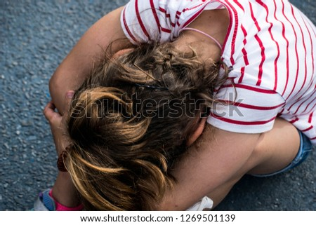 Sad and angry girl with the face sitting on the floor with her head on her lap. Psicological abuse is forbidden at schools, bullying and abusive behaviours. #1269501139