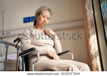 sad and depressed asian elderly woman sitting alone in wheel chair with head down in nursing home