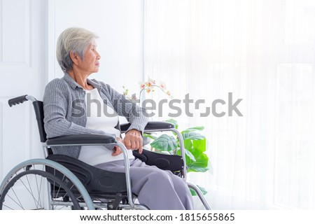 Sad and depressed asian senior woman in a wheelchair at home. Copy space on the window. Foto stock ©