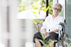 Sad and depressed asian senior woman sitting alone in wheelchair with head down feel lonely and bored,disabled old elderly with loneliness waiting for her family to come visit her at the nursing home