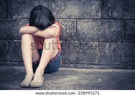 sad and depressed little Asian girl sitting in grunge room, filtered images