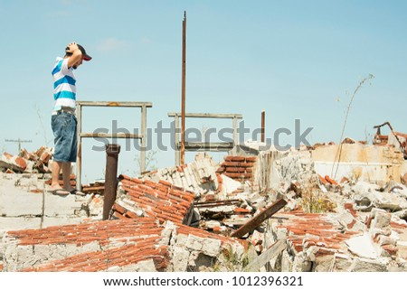 Sad and depressed man observes the debris left of his home after a natural disaster. #1012396321