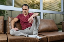 Sad and downcast Brazilian mature man (44 years old), sitting on the brown sofa, with a large window pane behind.