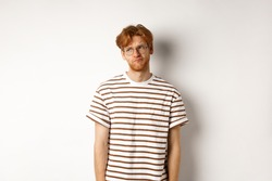 Sad and gloomy redhead man looking upper left corner, sulking and feeling like loser, standing over white background
