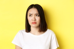 Sad and jealous asian girl sulking, frowning and looking left with upset face, standing over yellow background