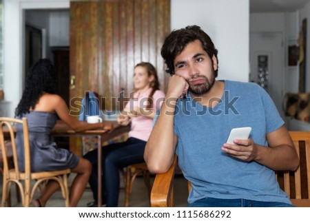 Sad and lonely hipster man waiting for text message of girlfriend