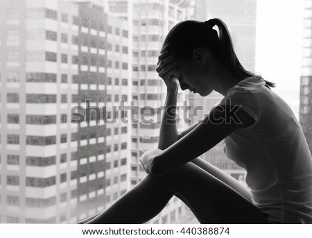 Shutterstock Sad and lonely woman in the city sitting next to a window.