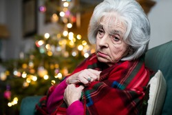 Sad And Lonley Senior Woman Unhappy About Spending Christmas At Home Alone Wrapped In Blanket
