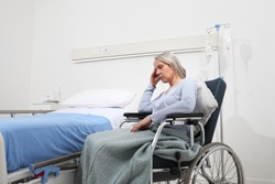 sad and pensive elderly woman abandoned and forgotten isolated on wheelchair near bed in hospital room, concept of loneliness and old age