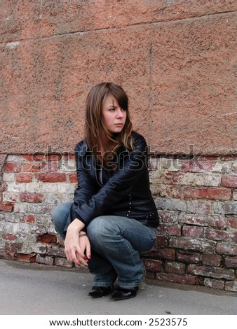 Sad and Pretty Girl sitting alone near grunge wall