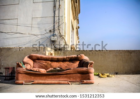 Sad and rustic lonely place with a shabby discarded empty couch that is torn and dirty with tangled wires on the back wall with a lot of empty space for copy
