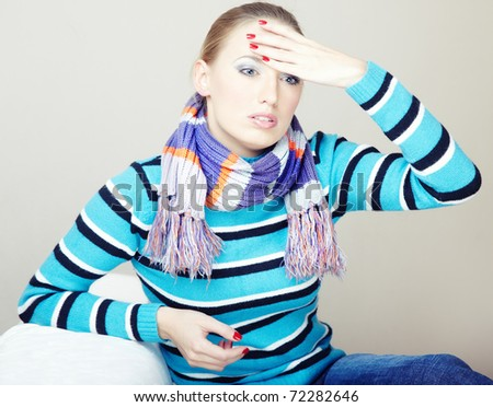 Sad and sick woman sitting indoors. Natural colors