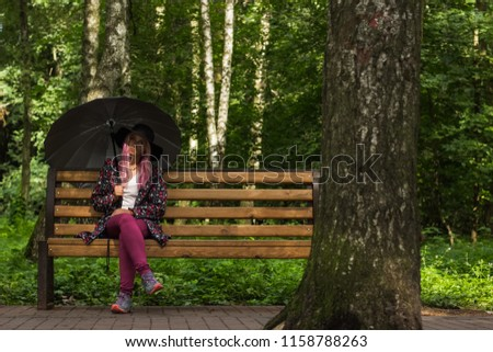 sad and sorrow concept of melancholy young beautiful girl with pink hair portrait under umbrella with face in shadow from black hat sit alone on wooden bench in outdoor park forest nature environment